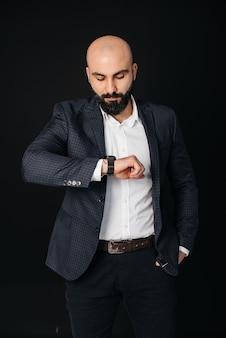 Um jovem barbudo, de camisa branca e jaqueta, encosta-se a uma parede preta.