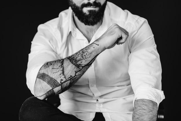 Um jovem barbudo em uma camisa branca e tatuagens fica em um fundo preto. preto e branco.
