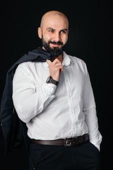 Um jovem barbudo em uma camisa e jaqueta branca está contra um fundo preto.
