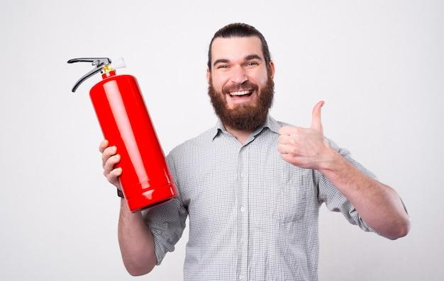 Um jovem barbudo está olhando e sorrindo para a câmera segurando um extintor de incêndio e uma pancada perto de uma parede branca