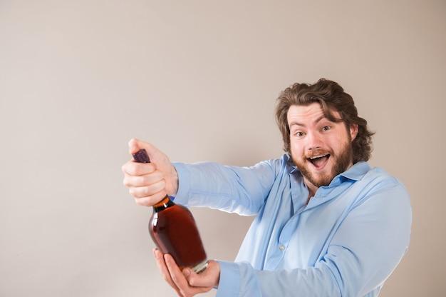 Um jovem barbudo feliz segurando uma garrafa de conhaque isolada em um fundo cinza claro