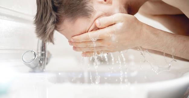 Um jovem barbudo lavando o rosto com respingos na pia do banheiro, rotina matinal