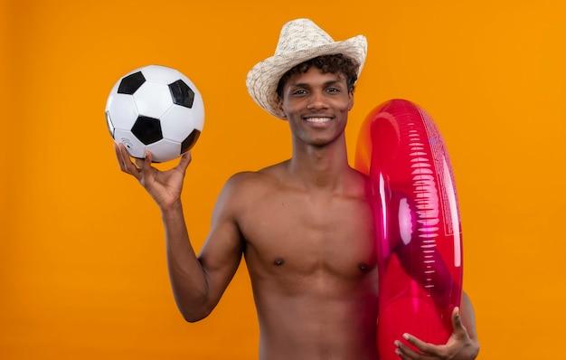 Um jovem bonito, alegre, de pele escura com cabelo encaracolado, usando chapéu de sol enquanto segura um ringue de sinuca inflável e uma bola de futebol
