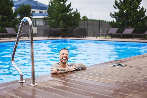 Um jovem bonito, brutal, elegante e elegante, sorridente, posando na piscina ao ar livre