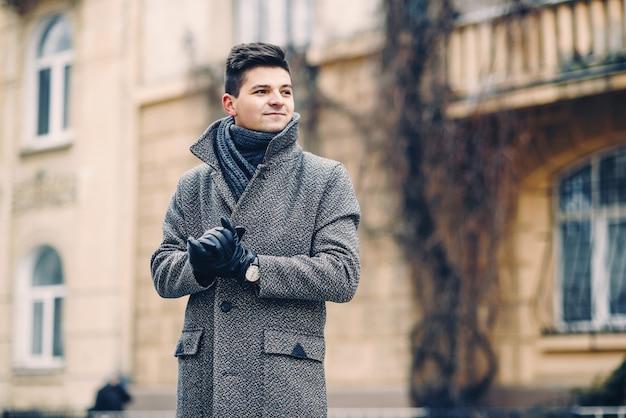 Um jovem bonito com um casaco quente, luvas de couro com um relógio em uma cidade a pé