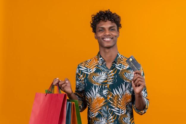 Um jovem bonito de pele escura com cabelo encaracolado em uma camisa estampada de folhas sorrindo segurando sacolas de compras e um cartão de crédito em pé