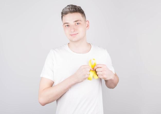 Um jovem bonito em uma camiseta branca está de pé em uma parede cinza, sorri e segura uma fita amarela nas mãos perto do coração - um símbolo de saúde