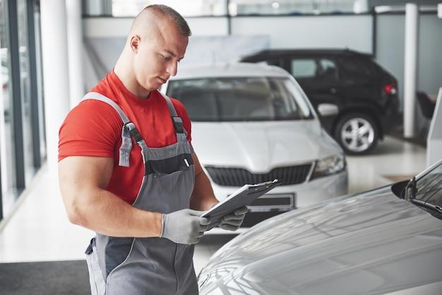 Um jovem bonito fala em uma concessionária de automóveis, consertando um carro em uma oficina.