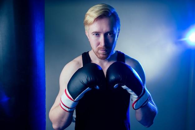 Um jovem boxeador masculino está praticando esportes no ginásio. boxeador, luvas de boxe em um fundo escuro. homem ataca