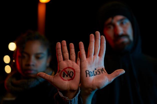 Um jovem branco e uma jovem negra exibindo uma mensagem escrita à mão contra o racismo. olhando seriamente para a câmera