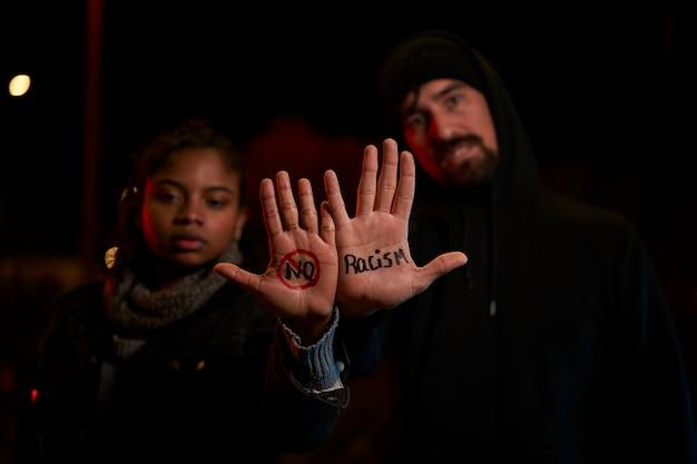 Um jovem branco e uma jovem negra exibindo uma mensagem escrita à mão contra o racismo.