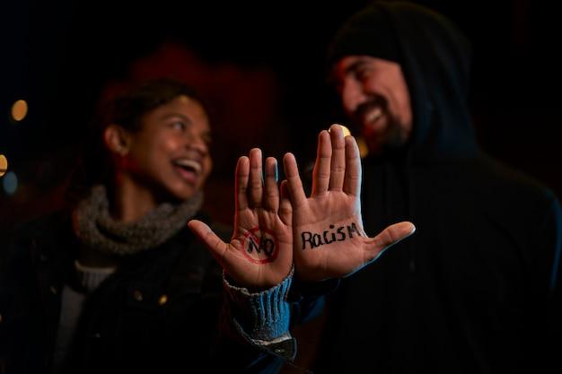 Um jovem branco e uma jovem negra sorrindo, mostrando uma mensagem escrita à mão contra o racismo.
