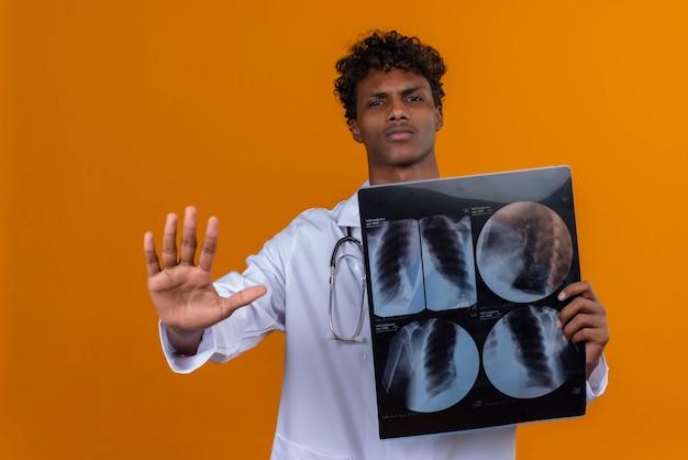 Um jovem bravo, bonito, de pele escura, cabelo encaracolado, jaleco branco e estetoscópio mostrando relatórios de raio-x