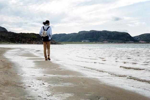 Um jovem caminha ao longo da costa do frio mar do norte. vista traseira. dia ensolarado.