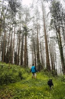 Um jovem caminhando com o casaco azul com o cachorro na floresta nebulosa