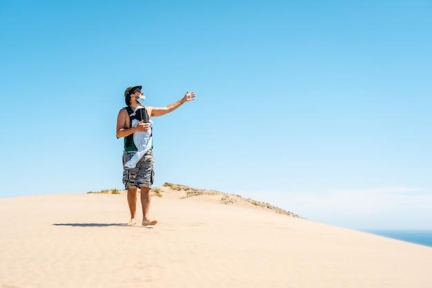Um jovem caminhando com seu filho na duna de areia da praia de monsul no parque natural cabo de gata, município de san jose, almeria