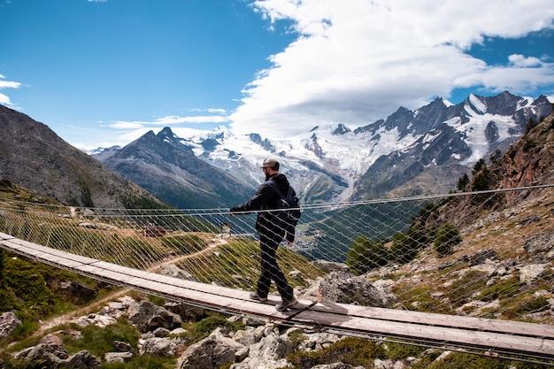 Um jovem caminhando em uma ponte pênsil na suíça, caminhando em uma bela paisagem viajando