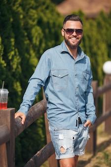 Um jovem caminhando no parque com limonada na primavera. dia de primavera. limonada.