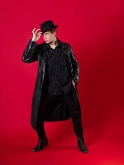 Um jovem carismático em roupas pretas, o herói de uma história noir,