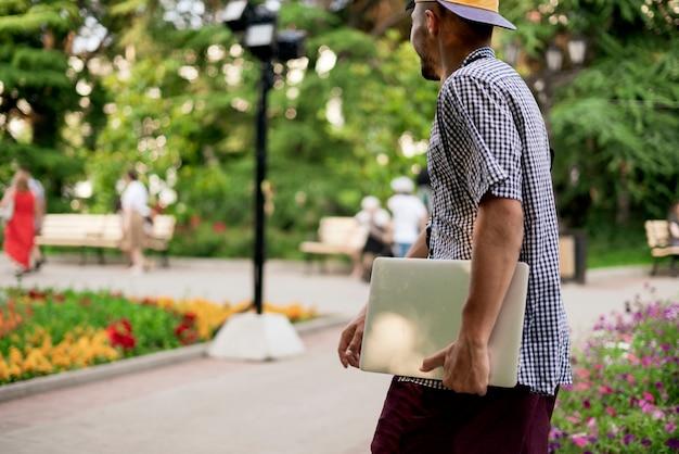 Um jovem carregando o laptop na cidade