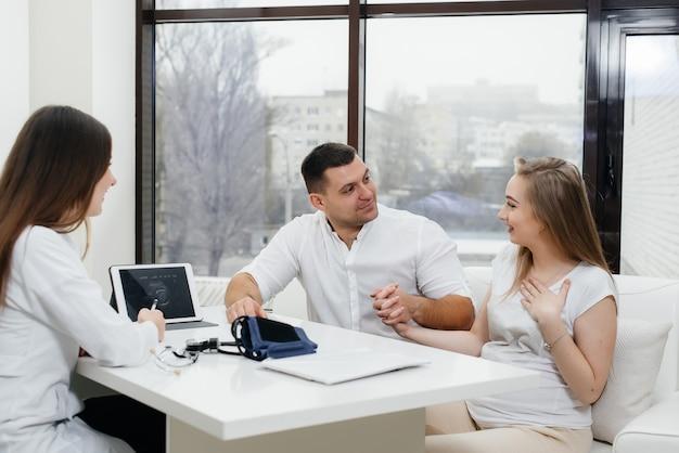 Um jovem casal à espera de um bebê para consultar um ginecologista após um ultrassom. gravidez e cuidados de saúde.