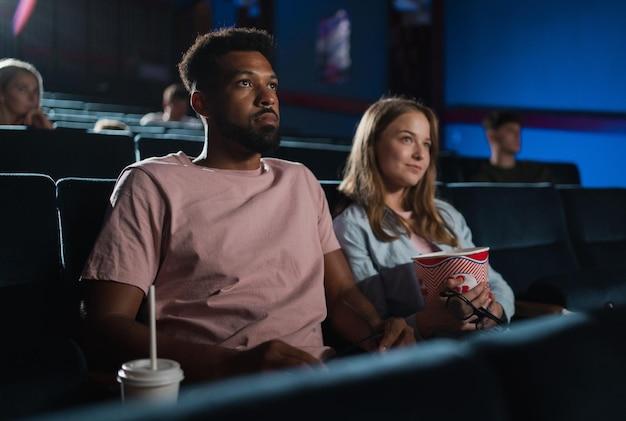 Um jovem casal alegre com pipoca no cinema, assistindo filme.