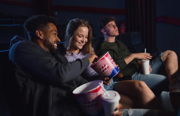 Um jovem casal alegre com pipoca no cinema, conversando.
