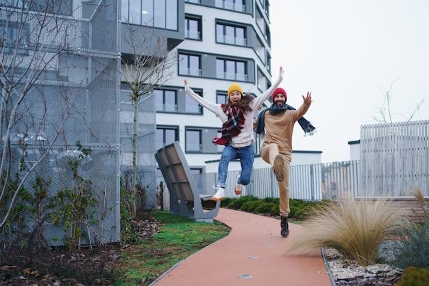Um jovem casal alegre de donos pulando ao ar livre em frente a um apartamento novo