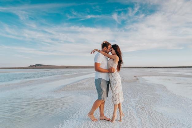 Um jovem casal amoroso caminha à beira-mar. recém-casados em uma viagem de lua de mel.
