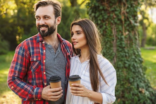 Um jovem casal amoroso feliz caminhando ao ar livre em uma floresta verde parque natural bebendo café.