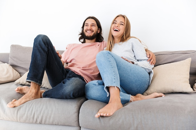 Um jovem casal amoroso feliz no sofá assistir a um filme de tv dentro de casa, em casa.