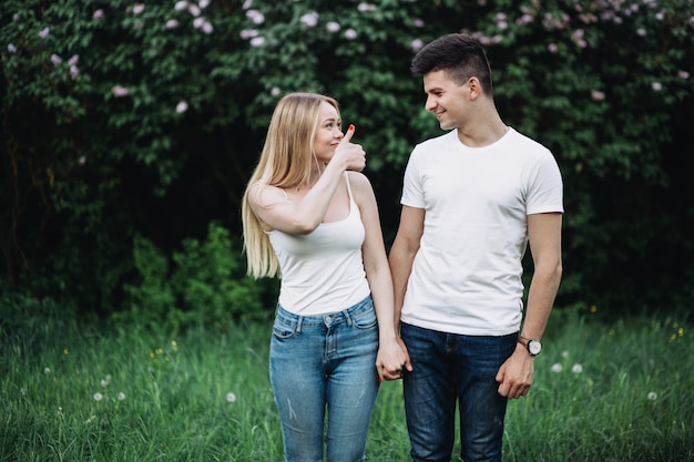 Um jovem casal apaixonado, de mãos dadas e rindo na frente de um arbusto de floração