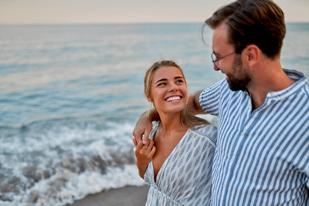Um jovem casal apaixonado está caminhando à beira-mar, curtindo um ao outro e suas férias, romanticamente passando alguns momentos na praia.