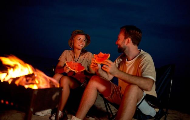 Um jovem casal apaixonado está sentado em cadeiras dobráveis perto da lareira, comendo melancia e se divertindo à noite na praia à beira-mar.