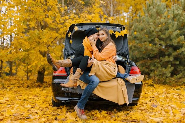 Um jovem casal apaixonado está sentado em um carro com o porta-malas aberto, se abraçando,