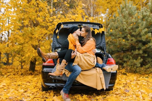 Um jovem casal apaixonado está sentado em um carro com o porta-malas aberto