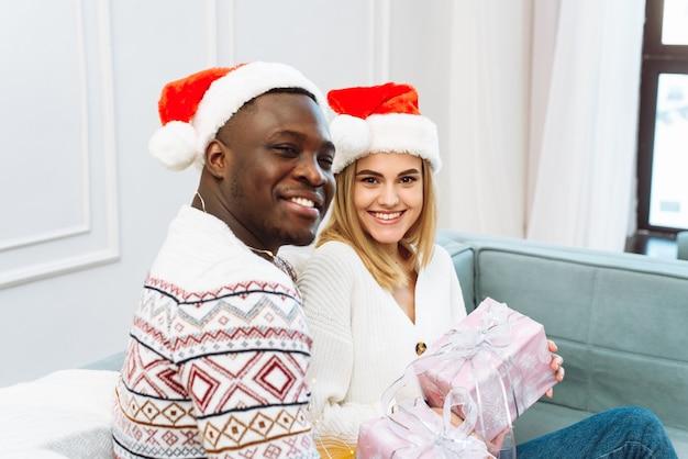 Um jovem casal apaixonado está sentado no sofá e trocando presentes. lindo casal jovem está comemorando em casa.