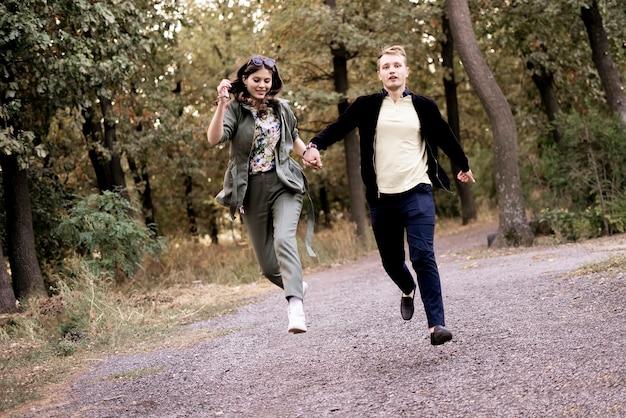 Um jovem casal apaixonado pula e voa, se divertindo, vida feliz