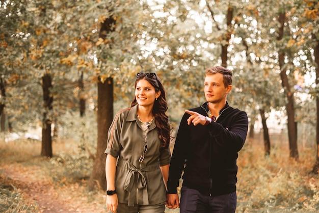 Um jovem casal aponta o dedo e olha para a floresta do parque, olha ali, procurando