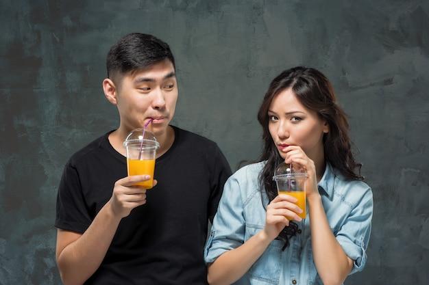 Um jovem casal asiático bonito com um copo de suco de laranja