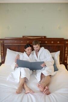 Um jovem casal assistindo a um álbum de fotos no quarto