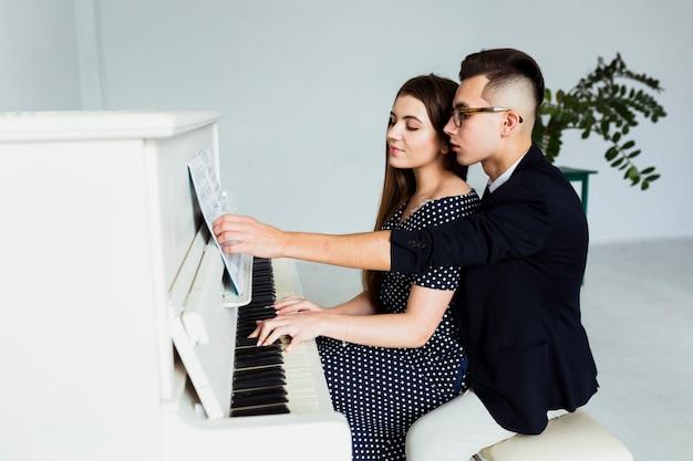 Um jovem casal atraente tocando juntos piano