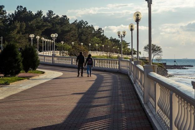 Um jovem casal caminha ao longo do dique gelendzhik ao pôr do sol. perspectiva uniforme da balaustrada.