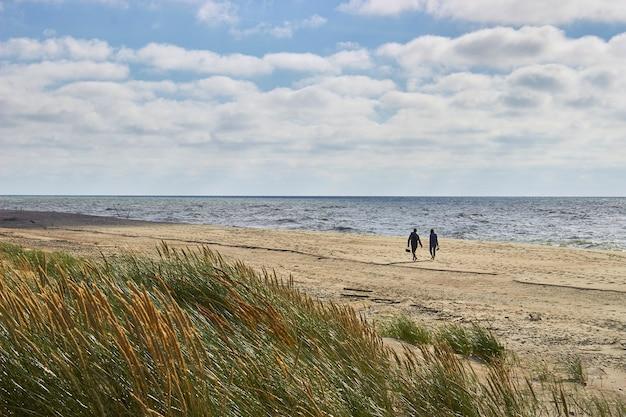 Um jovem casal caminha descalço à beira-mar após uma tempestade. contra o pano de fundo de um céu nublado e grama alta