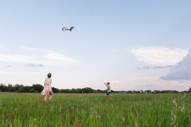 Um jovem casal caminha no campo perto da floresta. casal empinando uma pipa.