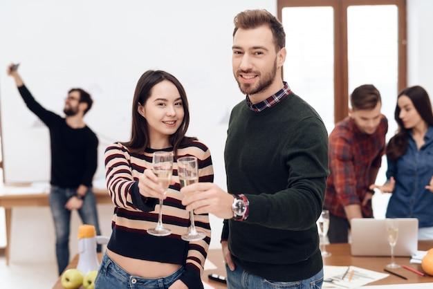 Um jovem casal celebra em uma festa corporativa