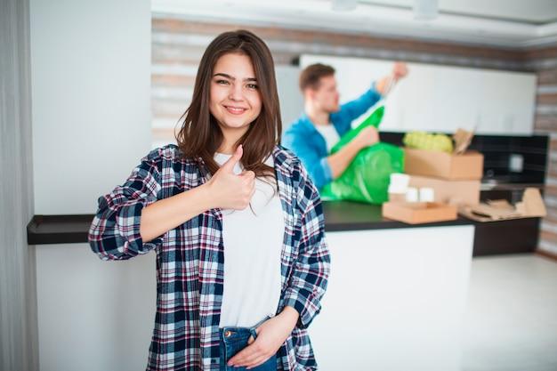 Um jovem casal classifica o lixo na cozinha. jovem e mulher estão classificando materiais recicláveis. jovem mulher aparecendo polegares.