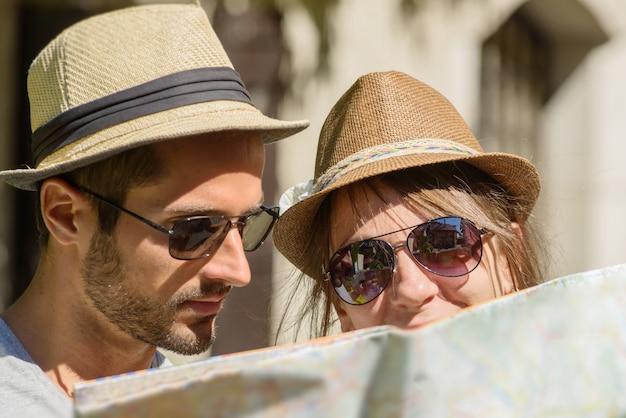 Um jovem casal com chapéus, olhando para um mapa