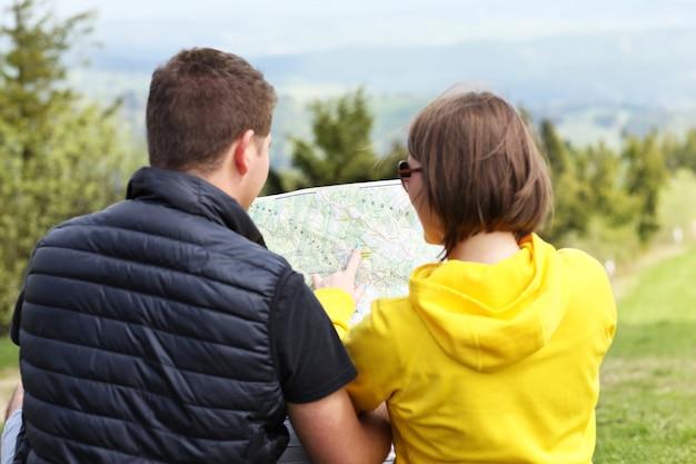 Um jovem casal com um mapa nas montanhas na polônia
