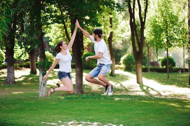 Um jovem casal comemora a vitória jogando jogo da velha no parque.
